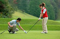 Male golfer sets a golf club held by a female partner on the tee ground