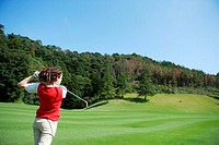 Rear view of a female golfer in action