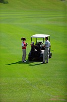 Couple holding golf clubs stand near a golf cart