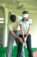 Male golfer teaching a woman to play golf