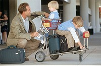 father at the airport with two sons