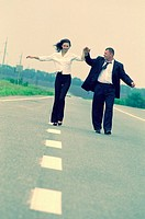 20 year old woman and 30 year old man walking on road