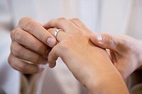 Groom placing wedding ring on brides finger (thumbnail)