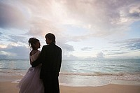 Newlyweds on beach at sunset