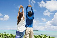Couple with arms raised by ocean