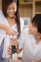 Couple opening wine bottle