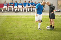 Referee talking to footballer