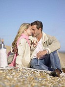 Couple having champagne on the beach