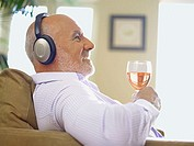 Man wearing headphones with a glass of wine
