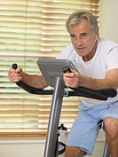 Man on exercise bike using telephone headset