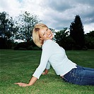 Blond woman sitting in park