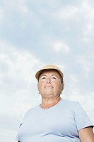 Senior woman against cloudy sky