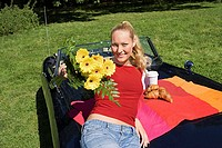 Woman on bonnet of convertible with flowers
