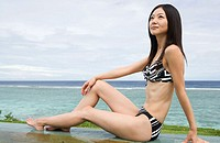 Woman in bikini by ocean (thumbnail)