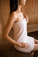 Woman in towel on wooden bench