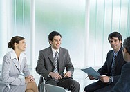 Business colleagues having meeting, smiling