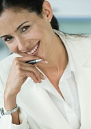 Businesswoman holding pen and smiling