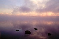 Calm lake with clouds and mist and rocks at sunrising
