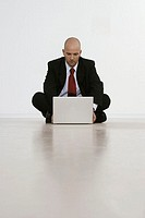 Businessman sitting on the floor with a laptop computer