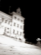 A portion of the Gothic-style NY State Capital Building in Albany, New York is captured at night with a ghostly blur