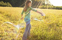 Girl making bubbles in a field (thumbnail)