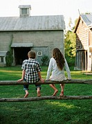 Boy and girl sitting on a fence, barn in the background (thumbnail)