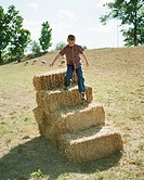 Boy coming down from a stack of hay bales (thumbnail)