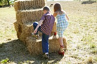 Boy and girl climbing a stack of hay bales (thumbnail)