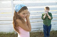 Girl and boy playing with tin cans and string telephone (thumbnail)
