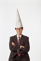 Businessman wearing dunce cap.