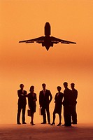 Businesspeople in group with airplane overhead.
