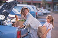 Mother and daughter putting groceries in car.