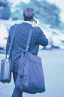 Man walking with luggage and talking on cellphone.