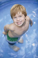 Boy in pool, portrait, aerial angle.