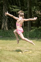 Girl running through sprinkler.