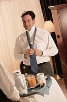 Businessman in hotel room receiving room service.