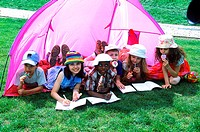 Young children lying in a tent drawing in books