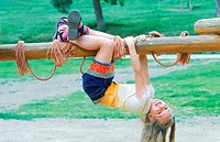 Young girl hanging from a jungle gym