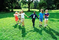 Young children holding hand walking on a lawn
