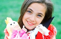 Young girl holding dolls and smiling