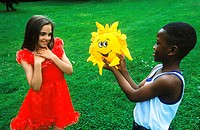 Young boy holding a toy stuffed sunflower in front of young girl