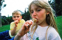 Young children eating lollipop
