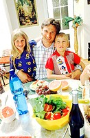 Portrait of a father with two children at a dinner table (thumbnail)