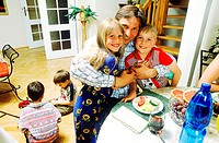 Mid adult man holding children at the breakfast table