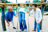 Two men holding young girl on a swing