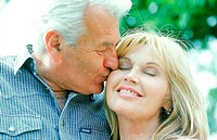 Close-up of an elderly man kissing a woman on the cheek (thumbnail)
