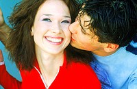 Close-up of a young man kissing a woman on the cheek