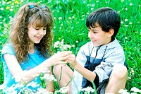 Boy and girl sitting in a garden together