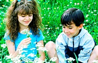 Young boy and young girl picking flowers (thumbnail)