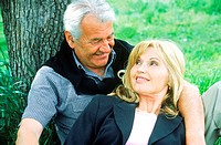 Mature couple sitting against a tree smiling (thumbnail)
